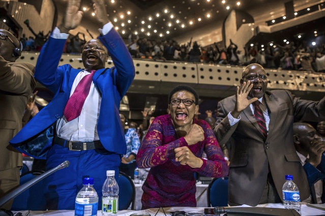 Zimbabwe's members of parliament celebrate after Mugabe's resignation on November 21, 2017 in Harare. Robert Mugabe resigned as president of Zimbabwe on November 21, 2017 swept from power as his 37-year reign of brutality and autocratic control crumbled within days of a military takeover. The bombshell news was delivered by the parliament speaker to a special joint session of the assembly which had convened to impeach Mugabe, 93, who has dominated every aspect of Zimbabwean public life since independence in 1980. (Photo by Jekesai Njikizana/AFP Photo)