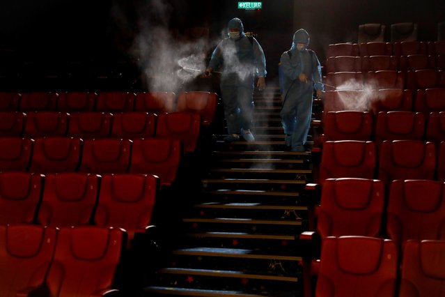 Staff of a cinema spray disinfectant at the cinema hall to prepare for reopening on July 1 in Kuala Lumpur, Malaysia, Friday, June 26, 2020. Malaysia entered the Recovery Movement Control Order (RMCO) after three months of coronavirus restrictions. (Photo by Vincent Thian/AP Photo)