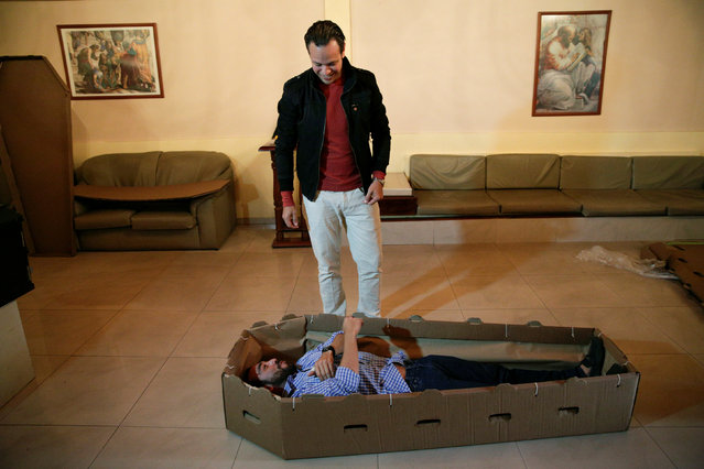 Elio Angulo (bottom C) lies inside a cardboard coffin next to Alejandro Blanchard as they introduce their product to potential customers at a mortuary in Valencia, in the state of Carabobo, Venezuela August 25, 2016. (Photo by Marco Bello/Reuters)