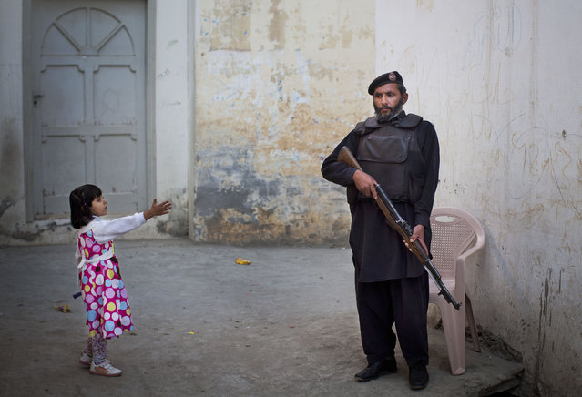 In this Wednesday, November 15, 2012 file photo, a young girl in her colorful dress reaches out to greet a Pakistani policeman securing the road outside Kainat Riaz's home in Mingora, Swat Valley, Pakistan. (Photo by Anja Niedringhaus/AP Photo)