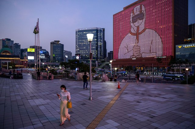People walk below a display on a building showing messages of support for health workers and the country amid the COVID-19 coronavirus pandemic outside Seoul station on July 8, 2020. (Photo by Ed Jones/AFP Photo)