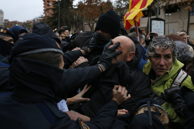 Catalan Mossos d'Esquadra officers scuffle with demonstrators as they cordon off the area around Lleida museum in the west of Catalonia, Spain, Monday, December 11, 2017. Police in Spain's northeastern Catalan city of Lleida have clashed with people protesting a judicial ruling ordering the city's museum to return 44 pieces of religious art to the neighboring regional government of Aragon. (Photo by Manu Fernandez/AP Photo)