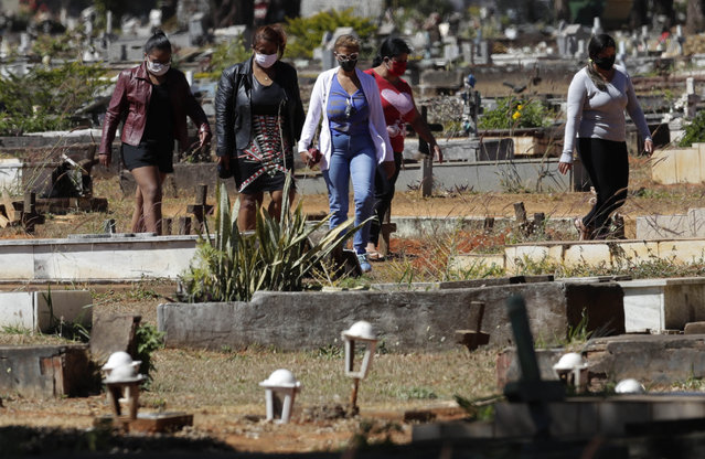 People arrive for the burial of Jose Mario de Souza Veiga, 83, whose family members said died of COVID-19, at the Campo da Esperanca cemetery on the border of the neighborhoods of Taguatinga and Ceilandia, in Brasilia, Brazil, Tuesday, July 21, 2020. (Photo by Eraldo Peres/AP Photo)