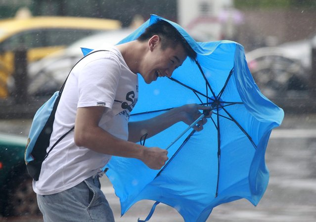 A man holds his umbrella while walking against strong winds caused by Typhoon Dujuan in Taipei, Taiwan, September 28, 2015. (Photo by Pichi Chuang/Reuters)