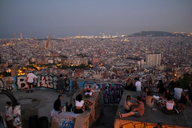 Tourists and locals gather at a lookout point, with a view of the city of Barcelona in the background, after regional authorities across Spain introduced fresh coronavirus disease (COVID-19) restrictions aimed at stamping out a surge in infections, in Barcelona, Spain on July 23, 2020. (Photo by Nacho Doce/Reuters)