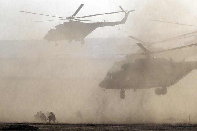 Russian military helicopters and troops take a part in a landing operation during military drills at the Black Sea coast, Crimea, Friday, September 9, 2016. (Photo by Pavel Golovkin/AP Photo)
