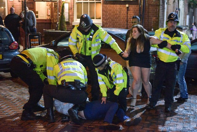 A girl pleads with police as they arrest a man in Birmingham, England on December 31, 2017. (Photo by Caters News Agency)
