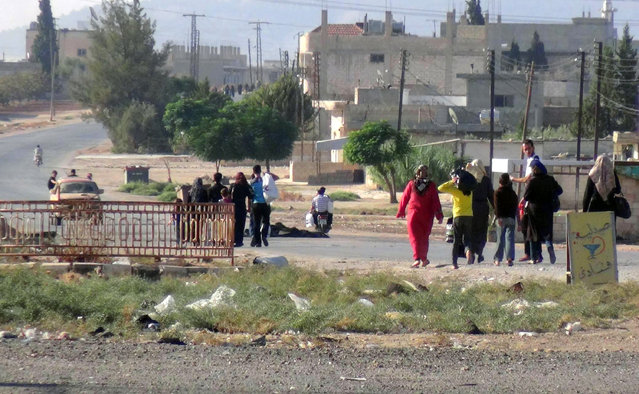 This photo provided by the Syria Press Center (SPC), an anti-government media group, shows civilians leaving the town of Suran, in Hama province, Syria, Thursday September 1, 2016. (Photo by Syria Press Center via AP Photo)