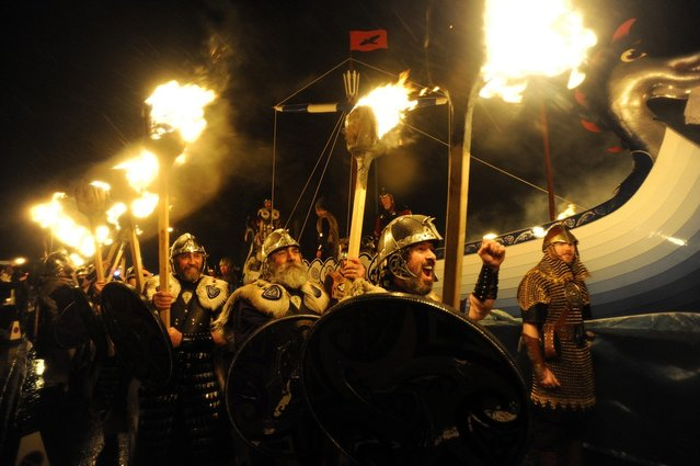 Members of the 2013 'Jarl Squad' take part in the annual Up Helly Aa festival which culminates in the burning of a Viking Galley in Lerwick, Shetland Islands on January 29, 2013. Up Helly Aa celebrates the influence of the Scandinavian Vikings in the Shetland Islands and has employed this theme in the festival since 1870. The event culminates with up to 1,000 'guizers' (men in costume) throwing flaming torches into their Viking longboat. AFP PHOTO / ANDY BUCHANAN        (Photo credit should read Andy Buchanan/AFP/Getty Images)