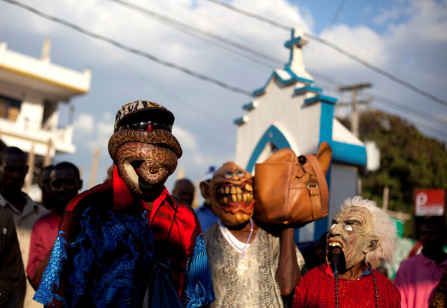 In this January 27, 2013 photo, snake handler Saintilus Resilus performs with a snake wrapped around his face as he and his assistants walk in the streets during pre-Lenten Carnival celebrations in Petionville, Haiti.  Haiti's snakes aren't venomous, but they have poisoned some relationships. Resilus' wife left him in 1991. (Photo by Dieu Nalio Chery/AP Photo/Matt Dayhoff)