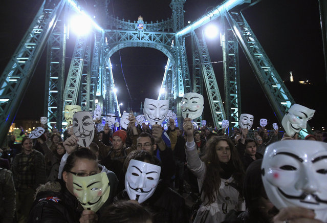 "Protesters hold up their Guy Fawkes masks on the Liberty Bridge during a demonstration by supporters of the Anonymous movement as part of the global ""Million Mask March"" protests, in Budapest, November 5, 2014. (Photo by Bernadett Szabo/Reuters)"