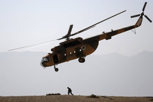 An Afghan National Army (ANA) helicopter flies over a soldier during a training exercise at the Kabul Military Training Centre in Afghanistan October 7, 2015. (Photo by Ahmad Masood/Reuters)