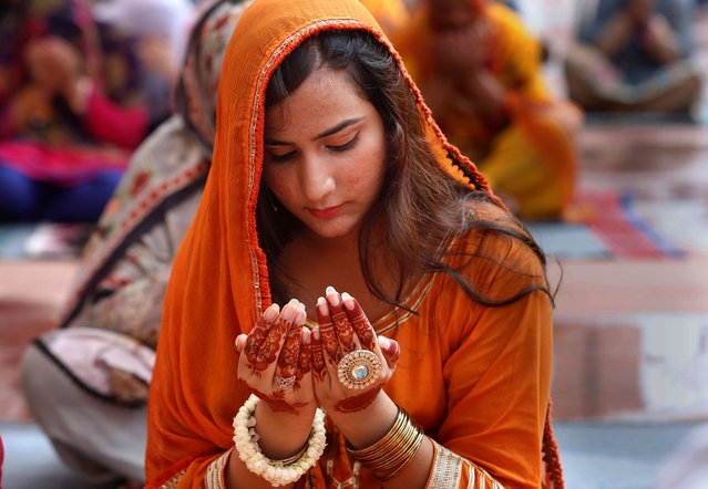 A woman prays during Eid al-Adha prayers at the historical Badshahi Mosque in Lahore, Pakistan, Saturday, August 1, 2020. During Eid al-Adha, or Feast of Sacrifice, Muslims slaughter sheep or cattle and distribute portions of the meat to the poor. (Photo by K.M. Chaudary/AP Photo)