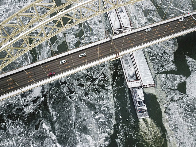 A barge cuts through ice on the Ohio River as it passes under the West End Bridge, along the North Shore district in Pittsburgh on Monday, January 1, 2018. (Photo by Haley Nelson/Pittsburgh Post-Gazette via AP Photo)