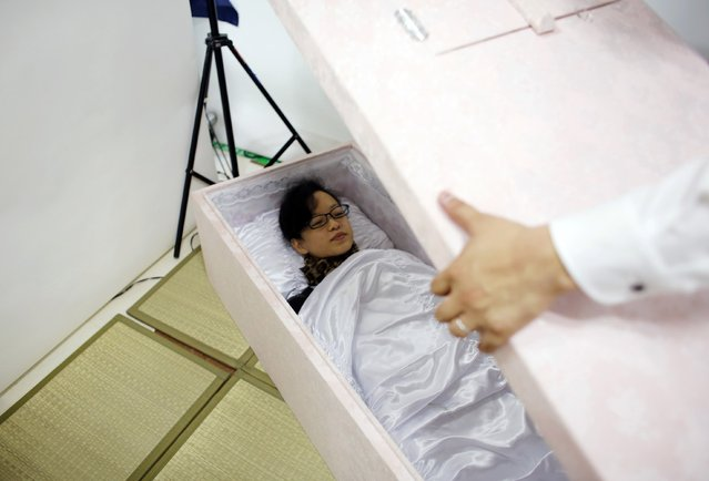 Natsumi Niki lies in a coffin to test it as a staff member prepares to place the lid on it during an end-of-life seminar held by Japan's largest retailer Aeon Co in Tokyo October 24, 2014. (Photo by Toru Hanai/Reuters)