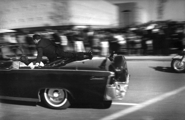 At 12:30 pm, just seconds after President John F. Kennedy and Texas Governor John Connally were shot in Dallas, Texas, the limousine carrying mortally wounded president races toward the hospital, on November 22, 1963. With secret service agent Clinton Hill riding on the back of the car, Mrs. John Connally, wife of the Texas governor, bends over her wounded husband, and Mrs. Kennedy leans over the president. (Photo by Justin Newman/AP Photo)
