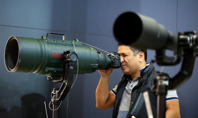 A visitor checks out a telephoto lens at the Sigma booth on the Photokina, the world's largest fair for imaging in Cologne, Germany, September 20, 2016. (Photo by Fabrizio Bensch/Reuters)