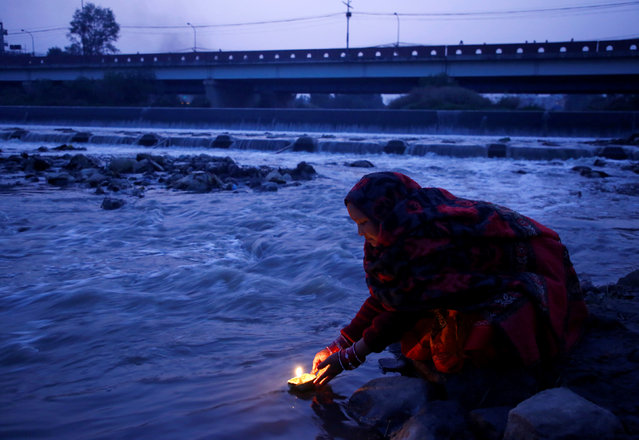 """A devotee offers an oil lamp as she offers prayer to the rising sun during the """"Chhath"""" festival at Bagmati River in Kathmandu, Nepal on October 27, 2017. (Photo by Navesh Chitrakar/Reuters)"""