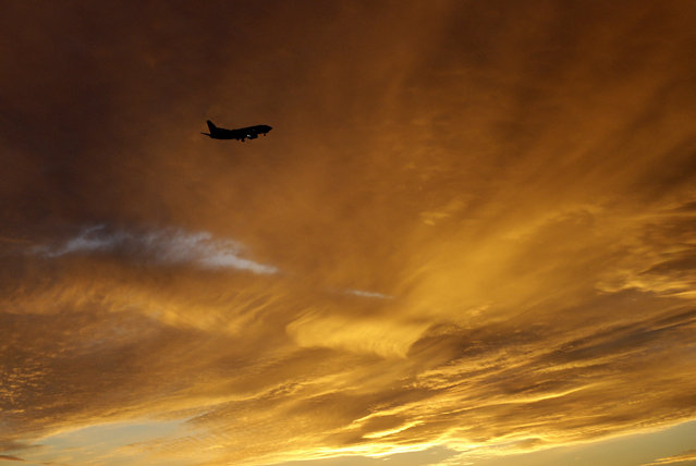 An airliner approaches Kansas City International Airport during sunset in Kansas City, Mo., Wednesday, November 12, 2014. (Photo by Orlin Wagner/AP Photo)