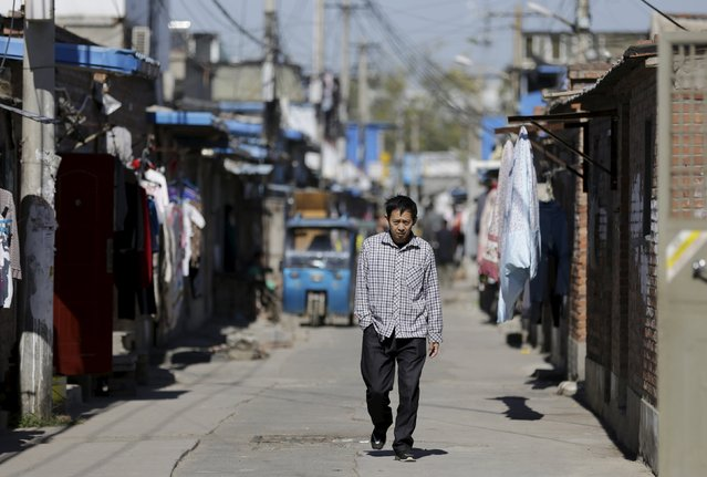 A man walks along an alley inside a residential area for migrant workers on the outskirts of Beijing, China, October 13, 2015. (Photo by Jason Lee/Reuters)