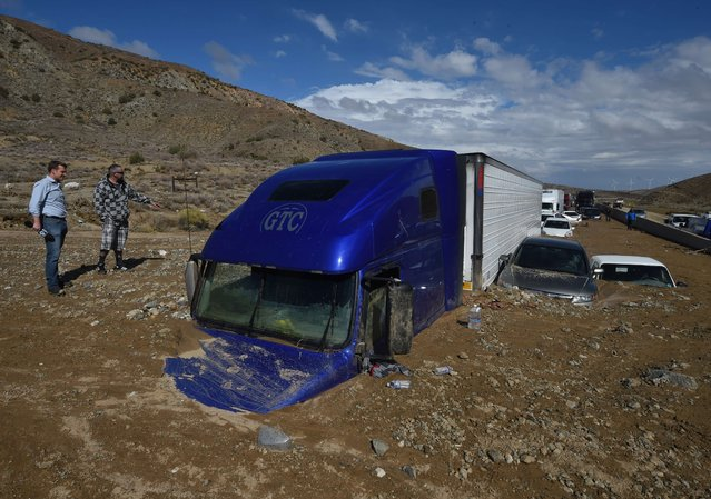 Reporters look vehicles stuck on a road after being trapped by a mudslide on California Highway 58 in Mojave, California on October 16, 2015, after torrential rains swamped the area and forced drivers and passengers to flee on foot. 75 tractor-trailers and two tour buses were among the 115 vehicles caught up in the disaster. (Photo by Mark Ralston/AFP Photo)