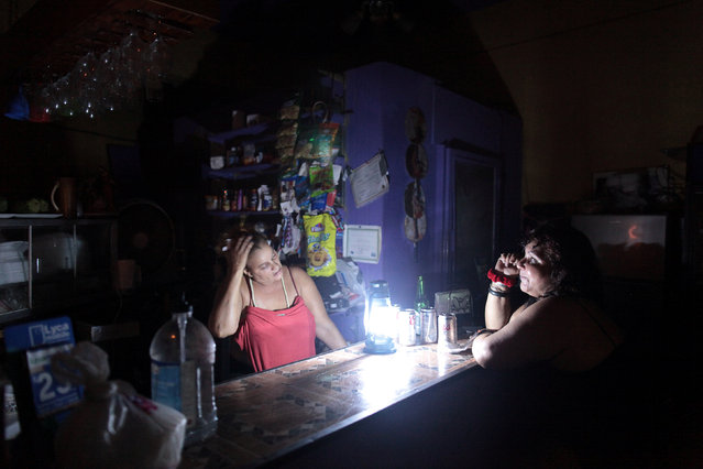 Flor Dalisa Contreras (L) talks with Virginia Rivas at a coffee shop during a power outage that affected several areas in the country, in San Juan, Puerto Rico, September 21, 2016. (Photo by Alvin Baez/Reuters)