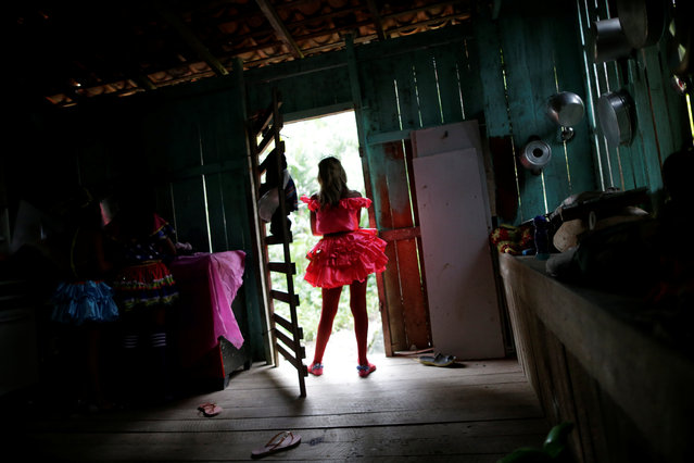 "A member of the ""Bloco Real Folia"" group is seen inside her house during Carnival of the Waters, where costumed and colorful boats navigate the river Jaituba, around the islands near the city of Cameta, Brazil on February 8, 2018. (Photo by Ueslei Marcelino/Reuters)"