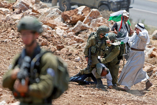 A Palestinian man argues with Israeli soldiers as they detain a demonstrator during a protest against Jewish settlements near Tulkarm in the Israeli-occupied West Bank on August 20, 2020. (Photo by Raneen Sawafta/Reuters)