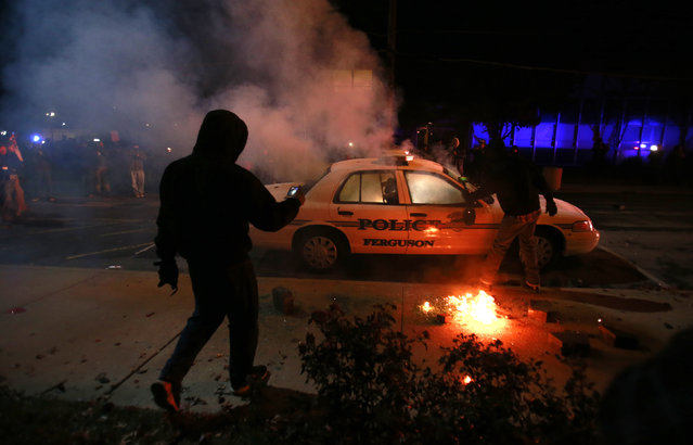 A protester videos a police car set on fire by protesters in Ferguson, November 25, 2014. (Photo by Adrees Latif/Reuters)