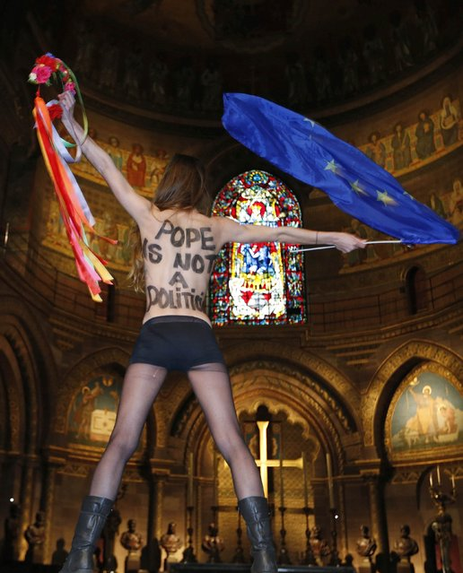 "A topless activist of women's rights group FEMEN holds a European flag as she demonstrates inside Strasbourg's Cathedral on the eve of Pope Francis' visit to European institutions, in Strasbourg, November 24, 2014. Pope Francis will address the European Parliament and the Council of Europe on Tuesday in Strasbourg. The words read, ""Pope is not a politician"". (Photo by Vincent Kessler/Reuters)"