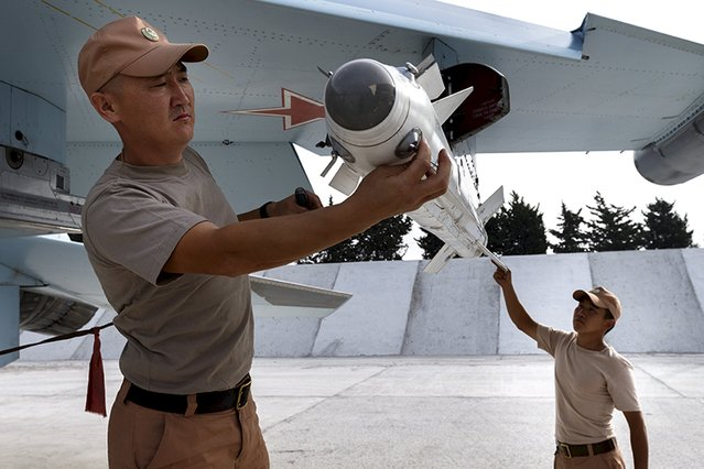 Russian ground staff members load a Sukhoi Su-30 fighter jet with weapons at the Hmeymim air base near Latakia, Syria, in this handout photograph released by Russia's Defence Ministry October 22, 2015. (Photo by Reuters/Ministry of Defence of the Russian Federation)