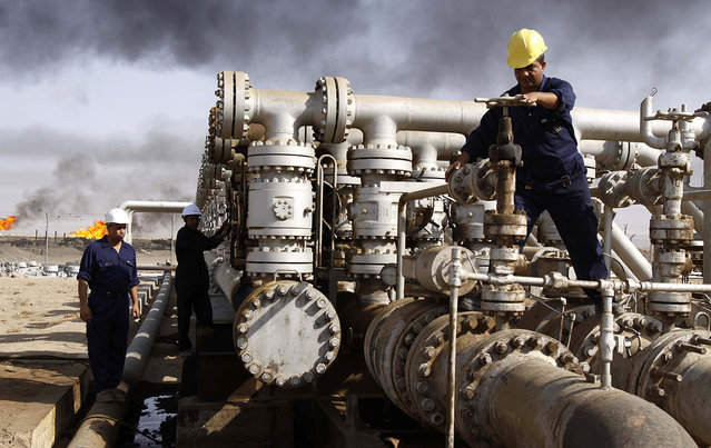 Iraqi workers at the Rumaila oil refinery, near the city of Basra, on December 13, 2009. (Photo by Nabil al-Jourani/AP Photo/The Atlantic)