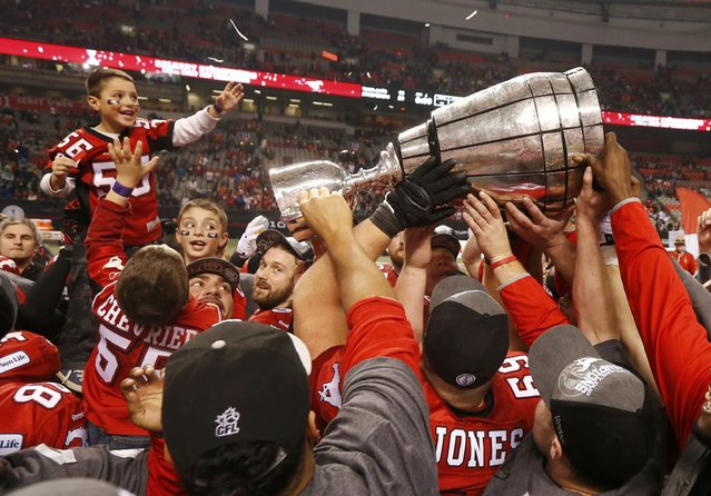 The Calgary Stampeders celebrate with the Grey Cup after defeating the Hamilton Tiger Cats in the CFL's 102nd Grey Cup football championship in Vancouver, British Columbia, November 30, 2014. (Photo by Mark Blinch/Reuters)
