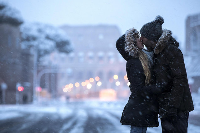 A couple kiss in front of Fori Imperiali covered by snow during a snowfall in Rome, Italy, 26 February 2018. Schools and public offices were closed and snow-removal crews were in place as Rome was on high alert for a first winter blast. Snowfall last week in Rome brought the capital to a standstill for days. (Photo by Angelo Carconi/EPA/EFE)