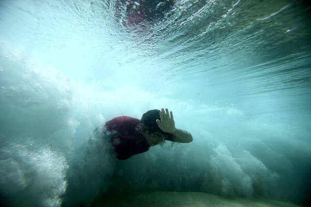 """A bodysurfer punches through a wave at the Ehukai sandbar near the surf break known as """"Pipeline"""" on the North Shore of Oahu, Hawaii, on March 21, 2013. (Photo by Hugh Gentry/Reuters)"""