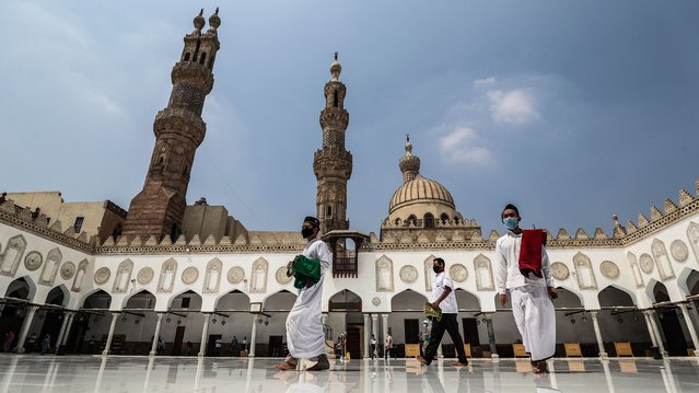 Muslim worshippers, mask-clad due to the COVID-19 coronavirus pandemic, arrive at the courtyard of the historic al-Azhar mosque in the centre of Islamic Cairo to perform the Friday prayers under new pandemic restrictions, in Egypt's capital on August 28, 2020. Egypt allowed Friday prayers to resume in major mosques under strict preventive measures, including mandatory masks for all worshippers, enforcement of social distancing, use of personal prayer rugs, and reduced sermon time at only 10 minutes. (Photo by Mohamed el-Shahed/AFP Photo)