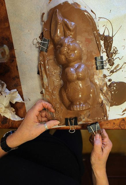 Darlene Eddy uses a mold to make a chocolate Easter bunny in her store Amazing Chocolates on March 28, 2013 in Hollywood, Florida. Americans spend roughly $1.9 billion on Easter candy, second only to Halloween in candy consumption. Around ninety million chocolate Easter bunnies are produced each year, from white to dark chocolate, and with an unlimited varieties of styles.  (Photo by Joe Raedle)