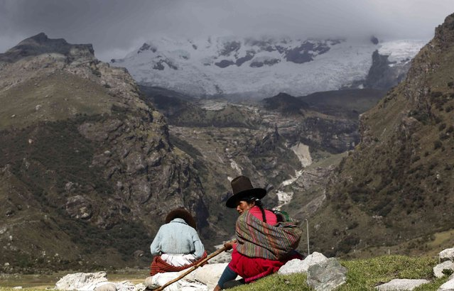 Shepherdess Narcisa Cornelio (R) and her daughter Nancy Condor rest in front of Hualcan glacier in Huascaran natural reserve in Ancash, November 29, 2014. Peru is home to 71 percent of the world's tropical glaciers, which are a source of fresh water for millions, but 22% of the surface area of Peruvian glaciers has disappeared in the past 30 years alone, according to The World Bank. (Photo by Mariana Bazo/Reuters)