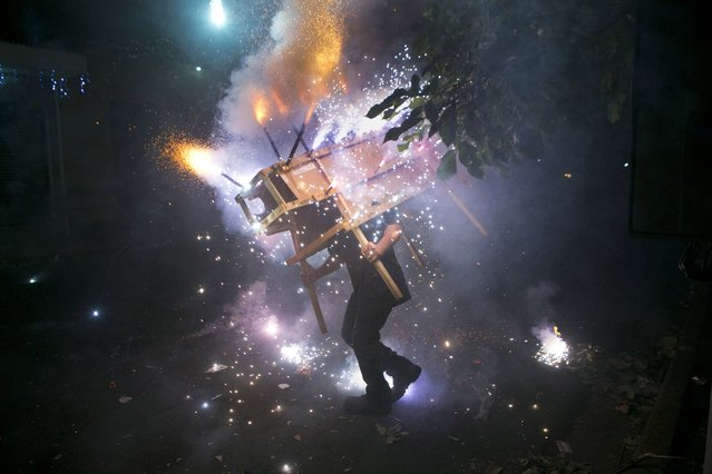 """A man runs with a """"toro encuetado"""", a structure resembling a bull and covered with exploding fireworks, as part of the celebrations in honor of the Virgin of the Immaculate Conception on her feast day in Managua, Nicaragua, early Monday, December 8, 2014. The Virgin of the Immaculate Conception is Nicaragua's patron saint. (Photo by Esteban Felix/AP Photo)"""