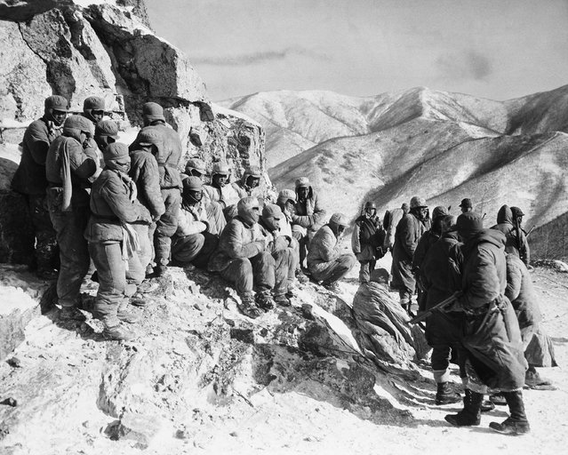 Chinese prisoners (left), rounded up by U.S. Marines (right), somewhere in the Frigid Mountains of North Korea, on December 22, 1950 appear cold in spite of their padded uniforms. One (left) is blowing on his hands. Others huddle with hands in sleeves. A more fortunate prisoner (lower right center) has a blanket. (Photo by AP Photo)