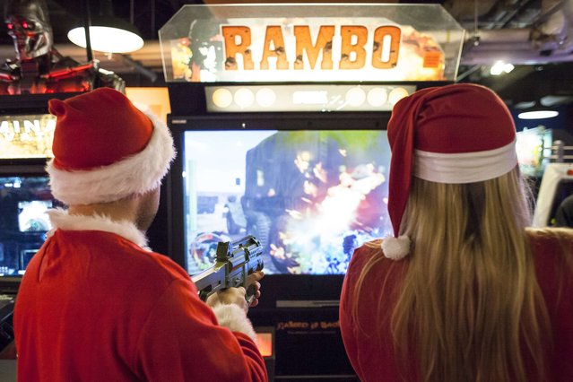 Santarchy participants Victor Celis (L) and Daley Smith (R) play a game at Gameworks in Seattle, Washington December 13, 2014. (Photo by David Ryder/Reuters)