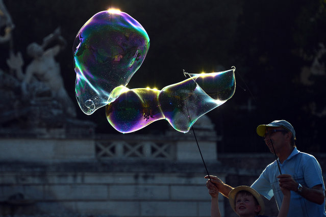 A street seller teaches a boy how to make soap bubbles, on Piazza del Popolo, a touristic square in central Rome at sunset on July 2, 2015. (Photo by Gabriel Bouys/AFP Photo)