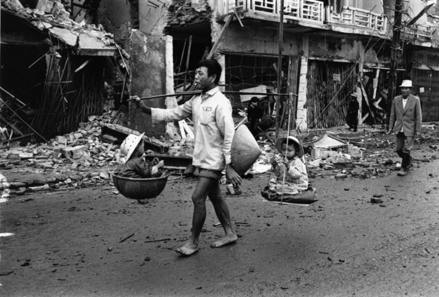 A Vietnam War refugee returns to Hue, carrying two children in baskets suspended from his shoulder, March 1968. (Photo by Terry Fincher/Daily Express/Hulton Archive/Getty Images)