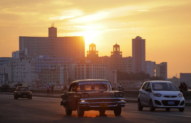 "Cars are driven as the sun sets over Havana's seafront boulevard ""El Malecon"", April 3, 2012. (Photo by Desmond Boylan/Reuters)"