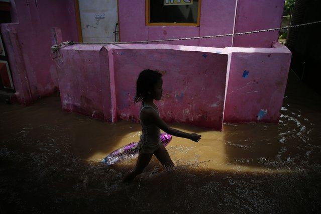 A child walks through a flooded street at Kampung Melayu residential area in Jakarta, December 23, 2014. (Photo by Reuters/Beawiharta)