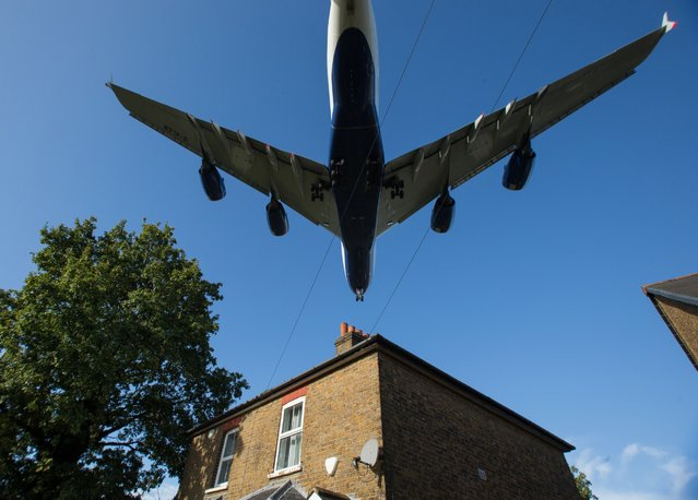A passenger aircraft passes over a residential house as it prepares to land at London Heathrow Airport in west London on October 17, 2016. Britain's government is considering whether to approve a third runway at Heathrow or expand air capacity in southeast England at another airport such as London Gatwick. (Photo by Daniel Leal-Olivas/AFP Photo)