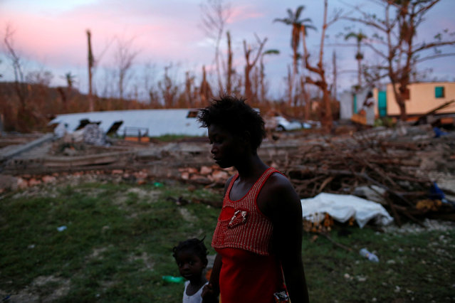 A woman and a girl walk next to a partially destroyed school used as a shelter after Hurricane Matthew hit Jeremie, Haiti, October 15, 2016. (Photo by Carlos Garcia Rawlins/Reuters)