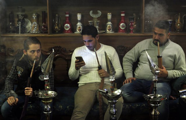 Men smoke shisha at a cafe in Baghdad December 17, 2014. (Photo by Thaier Al-Sudani/Reuters)