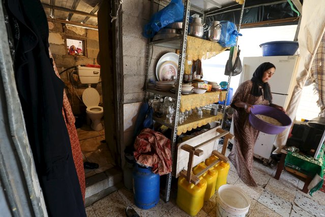 A woman passes near the entrance to a toilet in a makeshift shelter used by a Palestinian family in Khan Younis, in the southern Gaza Strip, October 13, 2015. The family's house was destroyed by, what witnesses said, was Israeli shelling during a 50-day war in the summer of 2014. (Photo by Ibraheem Abu Mustafa/Reuters)