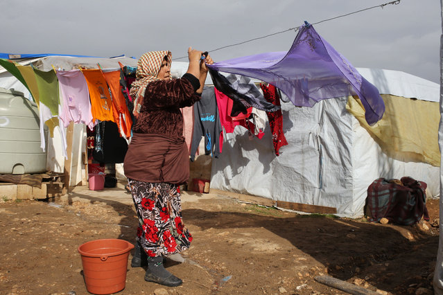 A Syrian woman hangs her laundry at a refugee camp in Deir Zannoun village, Bekaa valley, Lebanon, Tuesday, January 6, 2015. (Photo by Hussein Malla/AP Photo)